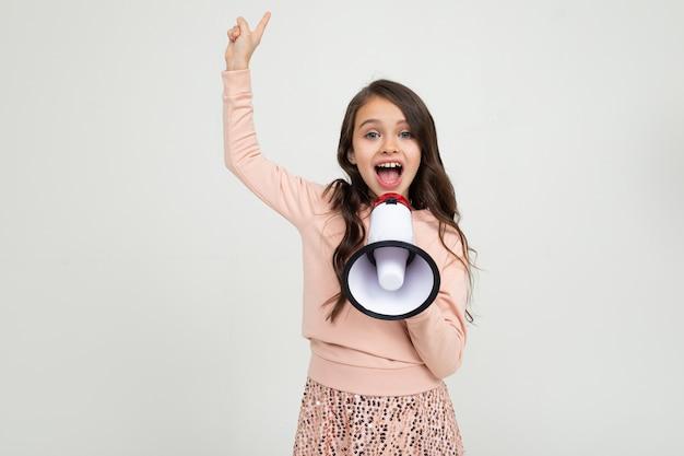 Fille émotionnelle européenne avec haut-parleur rapporte les nouvelles sur un mur de studio blanc avec espace vide