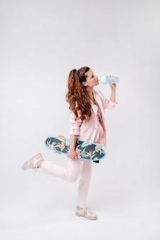 Une fille enceinte en costume rose avec une planche à roulettes dans ses mains boit du jus sur fond gris.