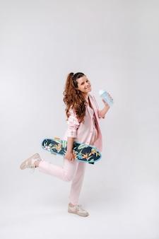 Une fille enceinte en costume rose avec une planche à roulettes dans ses mains boit du jus sur fond gris