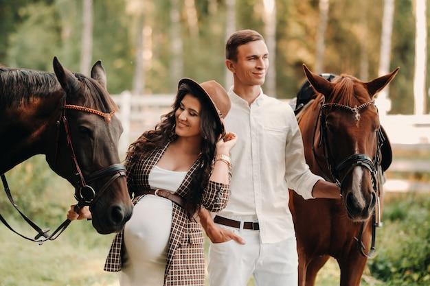 Une fille enceinte dans un chapeau et son mari en vêtements blancs se tiennent à côté de chevaux dans la forêt dans la nature.femme enceinte élégante avec un homme avec des chevaux.famille.