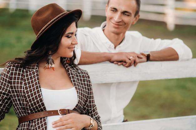 Une fille enceinte dans un chapeau et son mari en vêtements blancs se tiennent à côté d'un corral de chevaux au coucher du soleil.un couple élégant attend un enfant dans la nature.