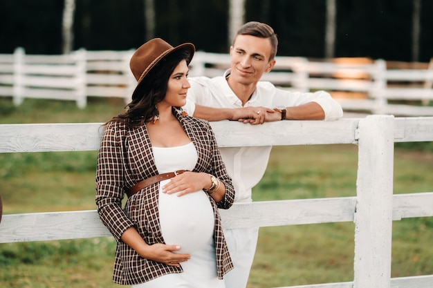 Une fille enceinte dans un chapeau et son mari en vêtements blancs se tiennent à côté d'un corral de chevaux au coucher du soleil.