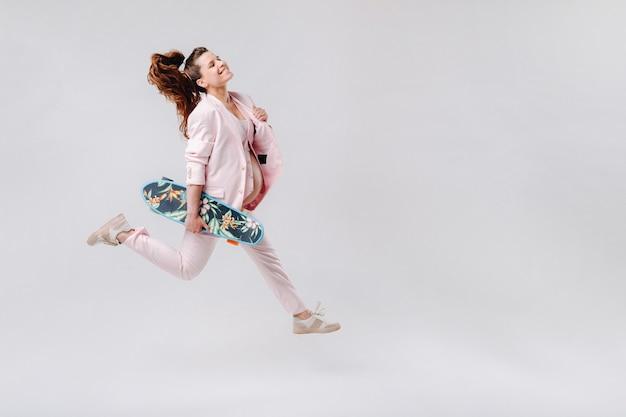 Une fille enceinte dans un costume rose avec une planche à roulettes dans ses mains saute sur un fond gris
