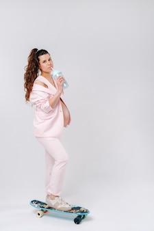 Une fille enceinte dans un costume rose avec une planche à roulettes dans ses mains se dresse sur un fond gris