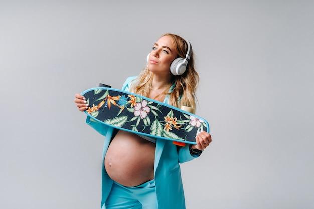Une fille enceinte dans un costume turquoise avec une planche à roulettes dans ses mains et un casque se dresse sur un fond gris