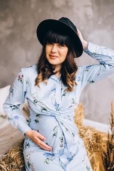 Fille enceinte dans une robe et un chapeau posant à la maison
