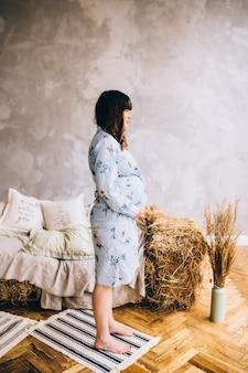 Fille enceinte dans une robe à la maison