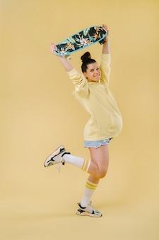 Fille enceinte dans une veste jaune avec une planche à roulettes dans ses mains sur fond jaune.