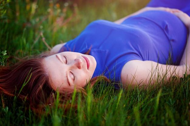 Fille enceinte est allongée dans l'herbe et rêve de sa grossesse