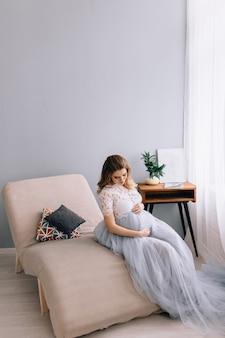 Fille enceinte est assise sur une chaise décorée