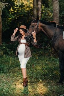 Fille enceinte avec un gros ventre dans un chapeau à côté de chevaux dans la forêt dans la nature. fille élégante en vêtements blancs et une veste marron.