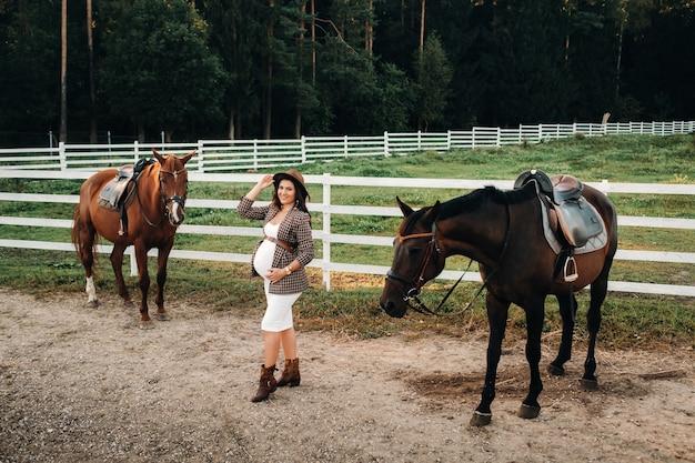Une fille enceinte avec un gros ventre dans un chapeau à côté de chevaux près d'un enclos dans la nature.