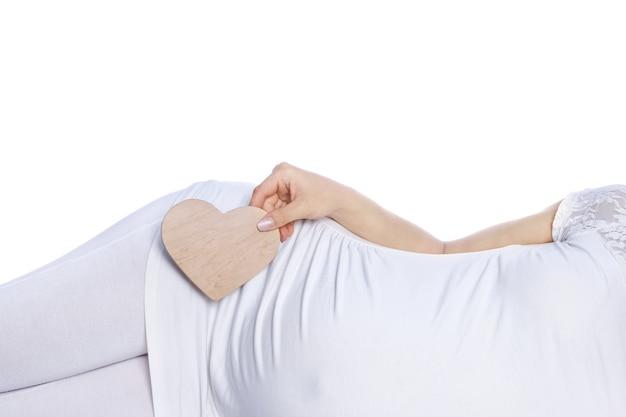 Une fille enceinte heureuse se trouve sur un mur blanc