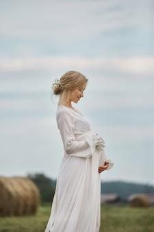 Une fille enceinte marche dans un champ près de meules de foin dans une longue robe blanche, une femme sourit et tient ses mains sur son ventre. la fille attend la naissance d'un bébé au neuvième mois de grossesse