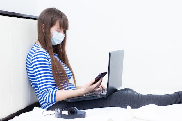 Fille enceinte avec un ordinateur portable sur le lit. travail à distance . santé et sécurité . fille et travail à distance. coronavirus.