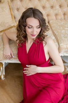 Fille enceinte en robe rouge