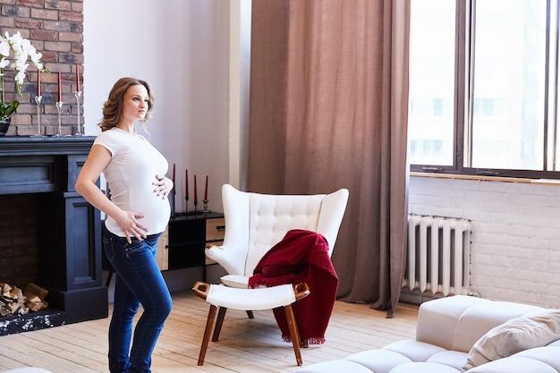 Une fille enceinte se tient debout dans le salon et touche son ventre.