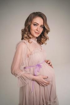 Une fille enceinte tient son ventre. une jeune mère attend la naissance d'un enfant. la femme embrasse doucement son bébé dans le ventre.