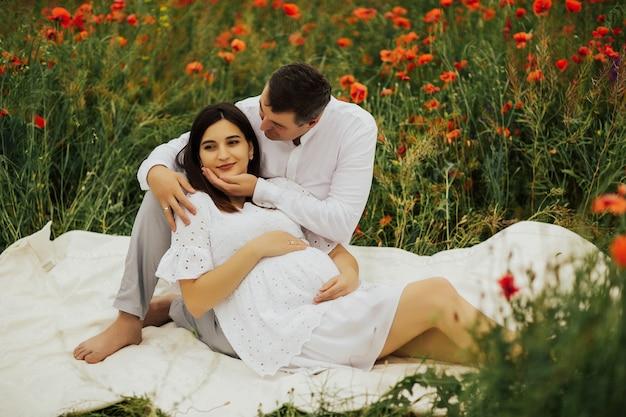 Fille enceinte avec un ventre allongé sur un plaid avec son mari dans un champ de pavot rouge