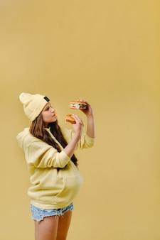 Fille enceinte en vêtements jaunes avec des hamburgers dans ses mains sur fond jaune
