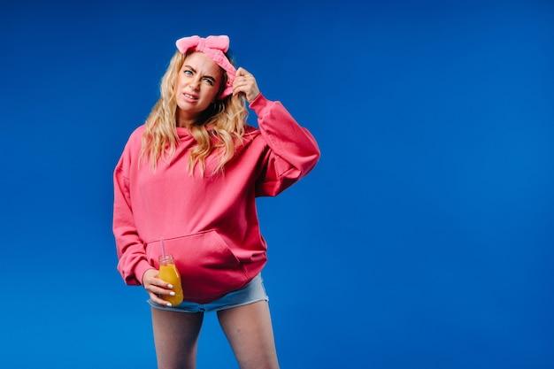 Fille enceinte en vêtements roses avec une bouteille de jus sur fond bleu.