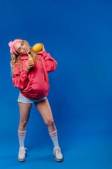 Fille enceinte en vêtements roses avec une bouteille de jus et un melon sur fond bleu.