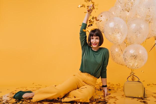 Fille enchanteresse aux cheveux courts jetant des confettis. portrait de joyeuse jeune femme s'amuser à son anniversaire.