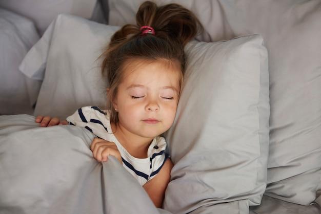 Fille endormie dans le lit
