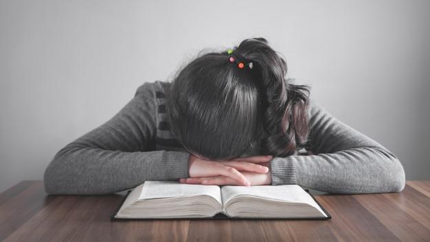 Fille endormie sur le livre ouvert.