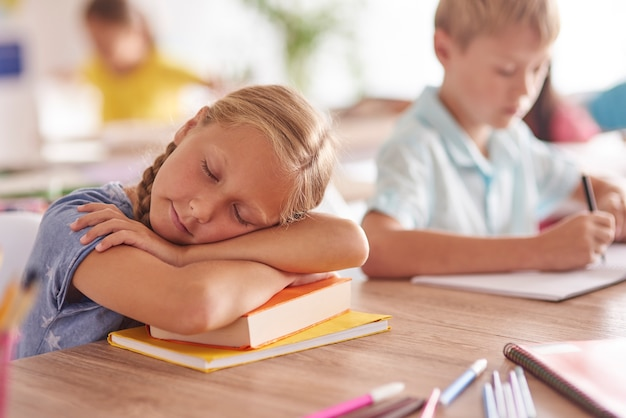 Fille endormie pendant la leçon