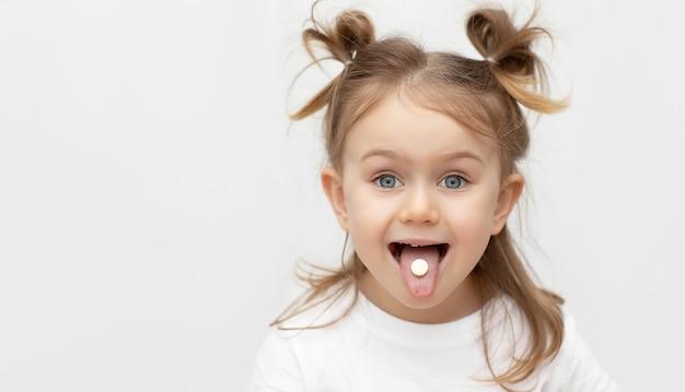Fille enfant adorable émotionnelle avec pilule ou bonbons sur la langue sur fond gris