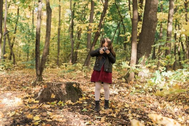 Fille enfant à l'aide d'un appareil photo à l'ancienne en automne nature photographe automne saison et loisirs