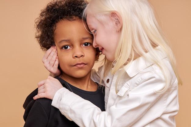 Fille enfant albinos sensible embrasse garçon africain isolé