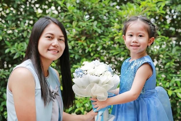 Fille enfant asiatique donnant le bouquet de fleurs pour sa mère dans le jardin.