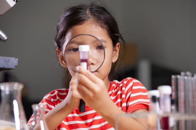 Fille enfant asiatique faisant une expérience chimique en laboratoire.