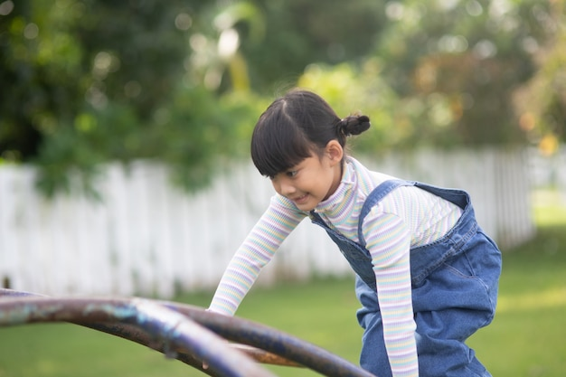Fille enfant asiatique jouant sur l'aire de jeux extérieure. les enfants jouent à l'école ou dans la cour de la maternelle. activité estivale saine pour les enfants.