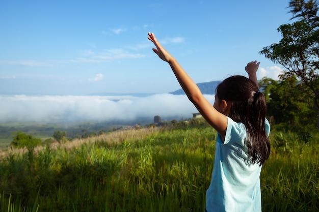 Fille enfant asiatique lève les bras en regardant la belle brume et la montagne avec fraîcheur et bonheur