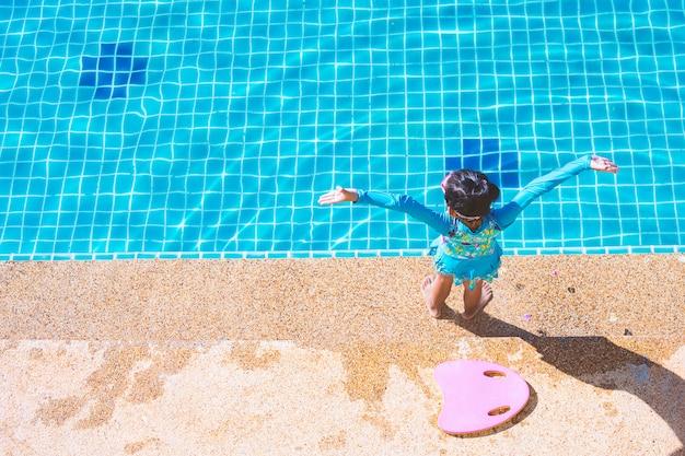 Fille enfant asiatique en maillot de bain debout et tenant flottant côté mousse au bord de la piscine.
