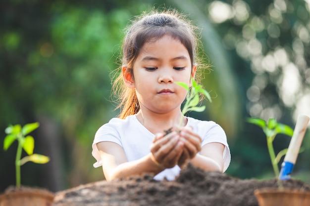 Fille enfant asiatique mignon tenant un jeune arbre pour planter dans le sol noir dans le jardin avec plaisir
