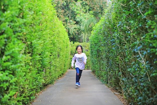 Fille enfant asiatique qui court dans le labyrinthe de jardin. enfant jouant dans un labyrinthe pour s'amuser et se divertir. vue arrière.