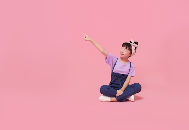 Fille enfant asiatique souriante pointant le doigt sur un espace vide à côté dans un mur isolé rose.