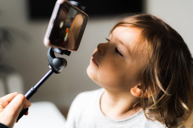 Fille enfant en bas âge à l'aide de téléphone avec bâton selfie pour appeler les grands-parents