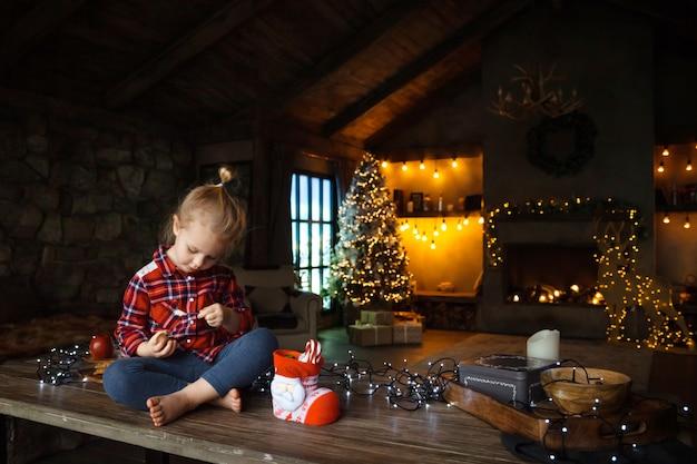 Fille enfant en bas âge au matin de noël, manger des bonbons d'un cadeau, assis sur une table en bois.