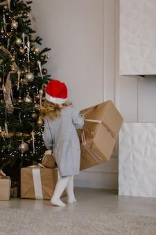 Fille enfant en bas âge drôle en attente de surprise de la boîte cadeau. concept de célébration de vacances d'hiver.