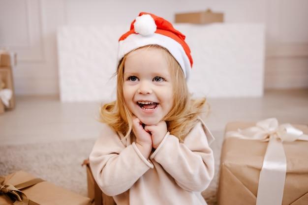 Fille enfant en bas âge drôle en attente de surprise de la boîte cadeau.