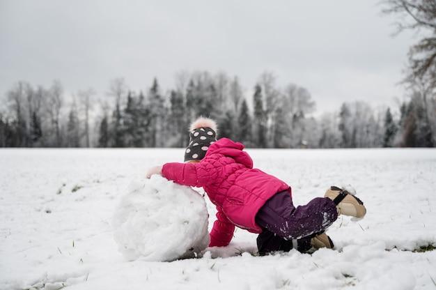 Fille enfant en bas âge jouant dans la belle nature enneigée faisant une grosse boule de neige