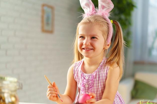 Fille enfant en bas âge avec des oreilles de lapin colorant des oeufs pour pâques