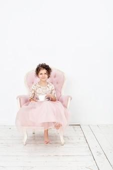 Fille d'enfant belle mignonne gaie et heureuse avec une tasse de thé sur une chaise rose