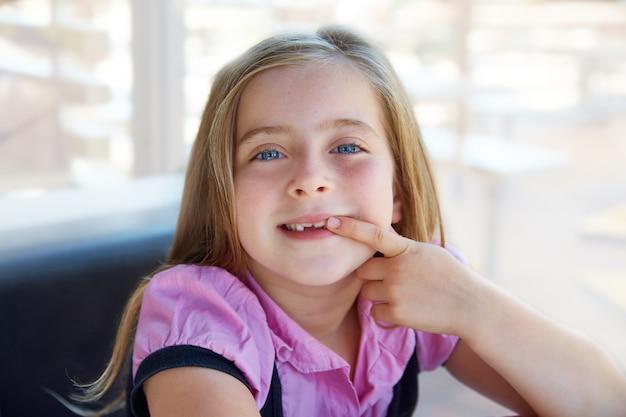 Fille d'enfant blonde heureuse montrant ses dents en retrait
