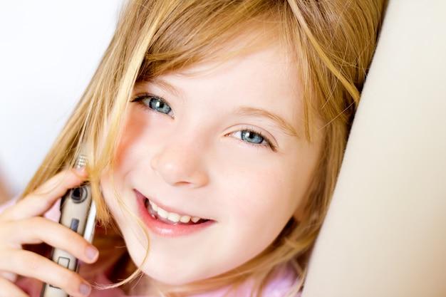 Fille enfant blonde parle de téléphone mobile